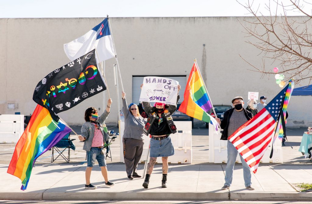 Protesters wave rainbow flags, an American flag and a coexist flag on the sidewalk across the street from the Tower Theatre. A counter protester is in the background waving a white flag containing a red cross.