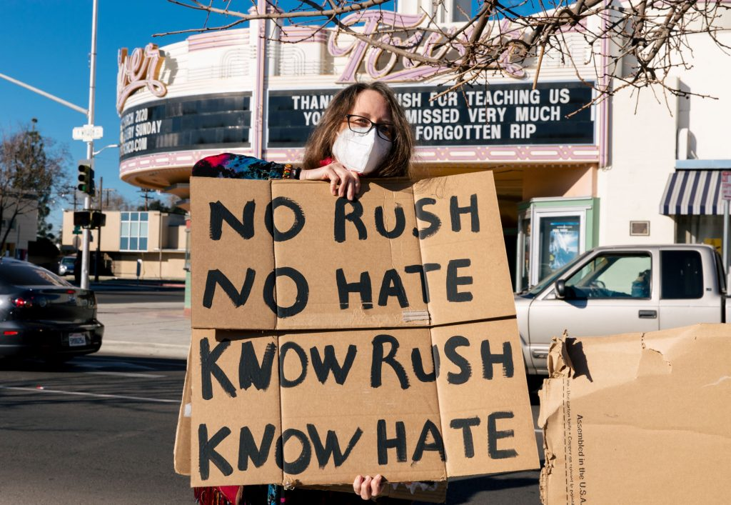"One protestor holds a cardboard sign with the words, ""No Rush, no hate. Know Rush, know hate."""
