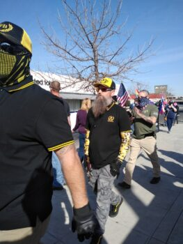 Men wearing black polo shirts with yellow stripes, some wearing black and yellow hats with the initials P.B., walk on a sidewalk and through a crowd of protestors. A few of the men wear yellow bandanas covering their face.